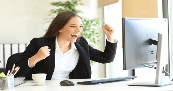 woman seated in front of her computer monitor, looking very excited with what she is seeing