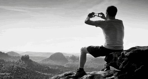 black and white photo of a man on a mountain top taking a photo with his Smart phone