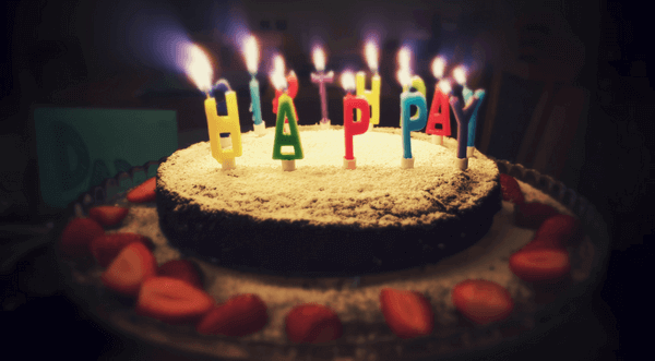 a birthday cake with candles spelling Happy Birthday