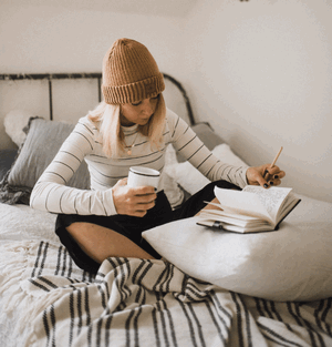 lady reviewing her writing while sitting on her bed with a coffee mug in one hand