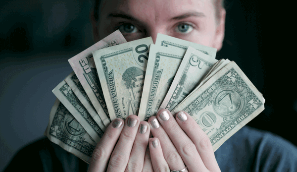 lady holding up several different American dollar bills, held fanned out in her hands, in front of her face